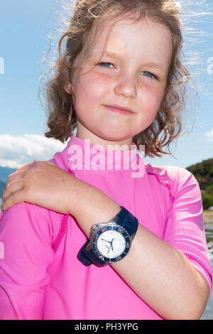 Junge Mädchen im Alter von 6 Jahre/6 Jahr alt ist ihr Vati/Vater mit Uhr/Zeit Stück auf einem sonnigen Strand an einem sonnigen Tag mit blauen Himmel tragen. (101) - Stockfoto