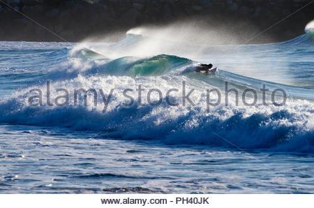 Ein surfer Schlachten mäßiger Wellengang - Paddeln durch Leistungsschalter' aus der Rückseite' - von Offshore Wind half zu erhalten; bei Turners Beach, Yamba, NSW, Australien. - Stockfoto
