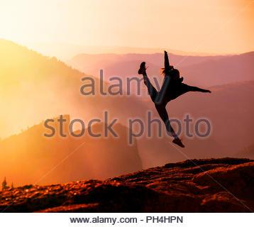 Silhouette einer Frau sprang auf den Felsen bei Sonnenuntergang - Stockfoto