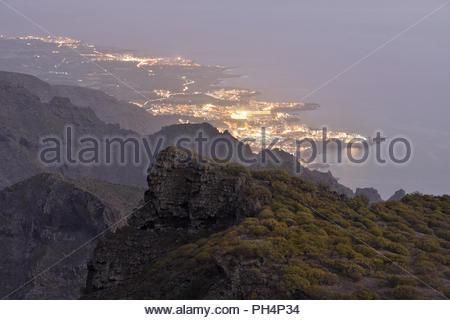 Städte von Los Gigantes und Puerto de Santiago leuchten in der Abenddämmerung. Erhöhte Ansicht vom Teno-gebirge im Nordwesten von Teneriffa Kanarische Inseln Spanien. - Stockfoto