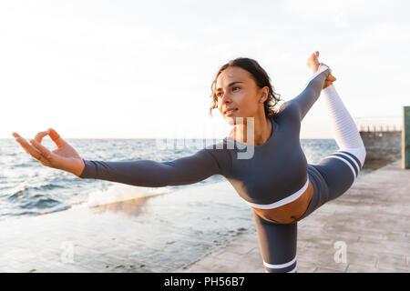 Bild des unglaublich starken jungen fitness Frau draußen in den Strand Yoga machen Dehnübungen. - Stockfoto