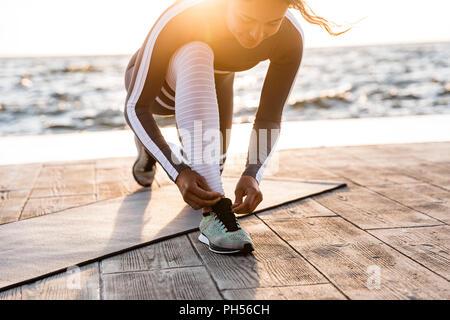 Bild von konzentrierten jungen fitness Frau draußen im Strand Schnürsenkel binden. - Stockfoto