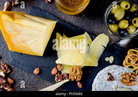 Verschiedene Arten von Käse auf dem Brett, Käseplatte aus einem Stück harten Käse, dünne Scheiben geschnitten, runden blauen Käse Kopf - Stockfoto