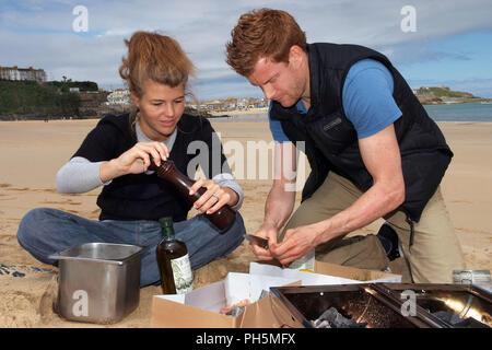 Tom & Amber Aikens kochen Fisch auf einen tragbaren Grill am Strand Carbis Bay, Cornwall, Großbritannien - Stockfoto