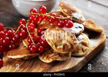 Pfannkuchen oder puffertjes mit Beeren und Ahornsirup auf rustikalen Tisch. - Stockfoto