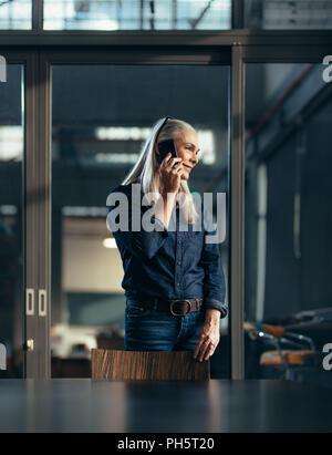 Portrait von Senior Business Frau, im Büro und im Gespräch über das Telefon. Weibliche Unternehmer ein Telefonanruf. - Stockfoto