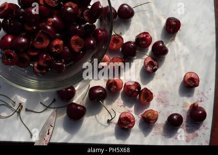 Frische reife Kirschen in Hälften geschnitten auf Weiß Schneidebrett oben Ansicht Küche noch leben Lebensmittelzubereitung - Stockfoto