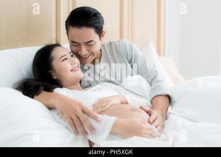 Stattliche asiatischer Mann und seine schöne schwangere Frau sind, umarmen und lächelnd, während zu Hause im Bett liegen. - Stockfoto