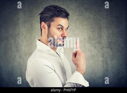 Gut aussehender bärtiger Mann mit dem Finger auf die Nummer Eins auf grauem Hintergrund ironisch - Stockfoto