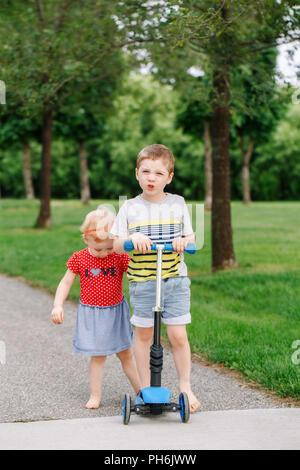 Zwei kleine Kaukasischen Vorschulkinder kämpfen im Park. Jungen und Mädchen können nicht ein scooter teilen. Ältere Geschwister Bruder nicht sein Spielzeug zu geben - Stockfoto