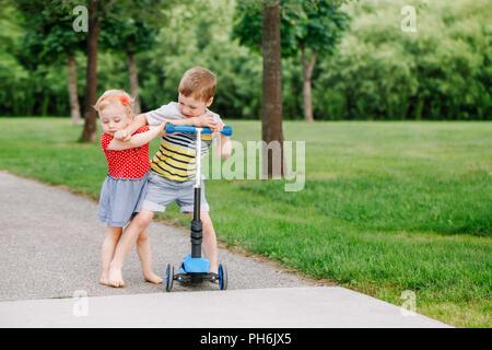 Zwei kleine Kaukasischen Vorschulkinder gegeneinander schlagen. Jungen und Mädchen können nicht ein scooter teilen. Ältere Geschwister Bruder nicht sein Spielzeug zu geben - Stockfoto