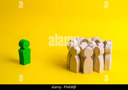 Die Holzfigur des Leader steht in der Nähe einer Menschenmenge. Kontaktaufnahme mit Mitarbeitern und Kunden, Führungsqualitäten. Erfolgreiche i - Stockfoto