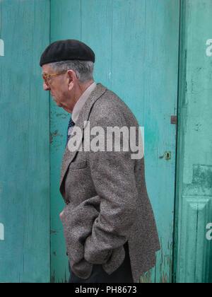 Profil Portrait von alten Mann mit einem spanischen Baskenmütze und eine intelligente grauen Sakko und Krawatte. Er ist zu Fuß vorbei an einem hellen türkisfarbenen Holztür in einer Straße in Menorca, Spanien. Der alte Mann schaut ein wenig besorgt - Stockfoto