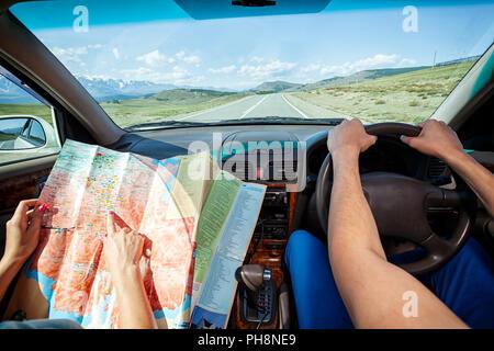 Mann und Frau im Auto fahren und Karte auf dem Land Fahrbahn zwischen Feldern mit braunem Gras und schneebedeckten Berge. Sonne scheint. Schießen - Stockfoto
