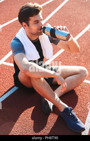 Erschöpft Sportler beendet am Stadion laufen, sich ausruhen, Trinken aus einer Wasserflasche - Stockfoto