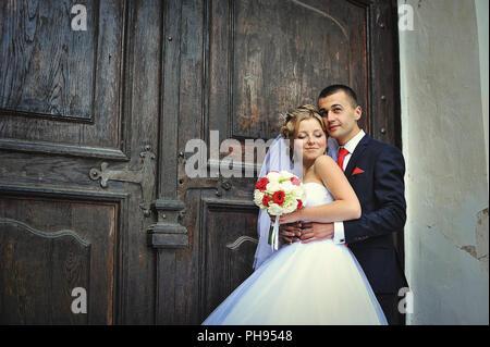 Hochzeitspaar auf dem Hintergrund der alten Holztür - Stockfoto