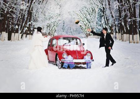 Hochzeitspaar im Winter in der Nähe von alte Oldtimer
