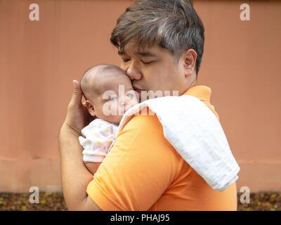 Portrait von Happy Asien Vater sein neugeborenes süßen Baby in Weiß gekleidet. Der Vater, der sein Baby mit Liebe und Sorgfalt. Seine Tochter - Stockfoto