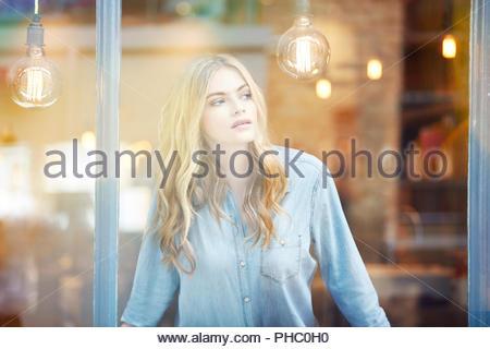 Junge Frau auf der Suche Fenster. - Stockfoto