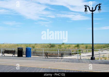 Holzsteg in der Nähe des Strandes mit einer Bank - Stockfoto