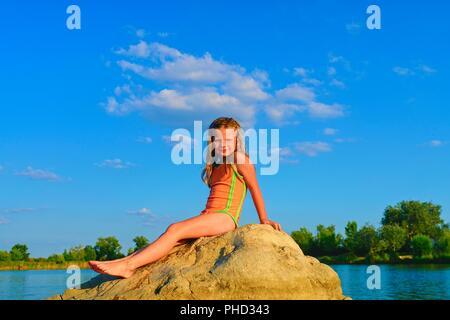 Adorable kleine Mädchen sitzt auf einem großen Stein im See an einem heißen Sommertag. Kind gekleidet im Badeanzug. Sommer und glückliche Kindheit Konzept. Kopieren Sie Raum in der strahlend blaue Himmel - Stockfoto