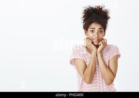 Innen- schuss von ängstlich unsichere attraktiv gebräunten Frau mit lockigem Haar, Gesicht berühren, Anheben der Augenbrauen und das Gefühl intensiver, besorgt oder Suchen nach etwas erschreckend, auf grauen Hintergrund posiert - Stockfoto