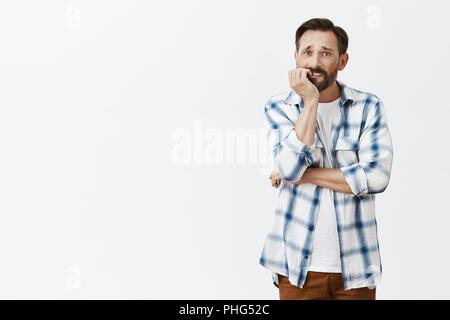 Mann, der versucht, ruhig Rauchen, Beißen, Fingernägel, während das Gefühl brauchen, um zu rauchen, runzelte die Stirn und starrte mit traurigen Ausdruck beiseite, Denken, Versuch, Gefühle zu steuern, stehen über grauer Hintergrund besorgt - Stockfoto