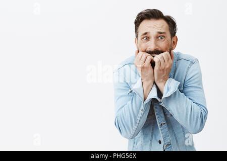 Mann nicht wieder, die meisten unheimlich Angst lebendig. Portrait von schüttelte und erschreckend ängstliche Kerl, beißen Fingernägel und bückte sich beim Stehen über grauer Hintergrund in Jeans Jacke, zu Tode erschrocken - Stockfoto