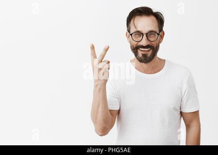 Indoor schoss der Schönen zuversichtlich und glücklicher Mann mit modischen Brille angezeigt Nummer zwei oder bis ihre Geste, breit grinsend über grauer Hintergrund, etwas zweimal - Stockfoto