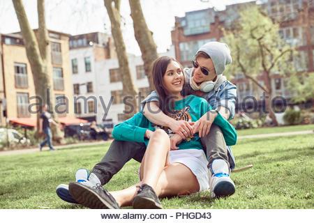 Teenage Paar zusammen im Park sitzen - Stockfoto