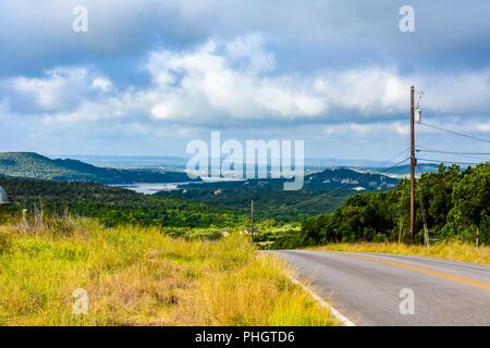 Land zurück Straße im Texas Hill Country mit Blick auf einen See, ausserhalb von Austin, TX. - Stockfoto