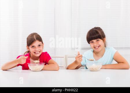 Süße kleine Mädchen sitzen und essen Müsli zum Frühstück. - Stockfoto