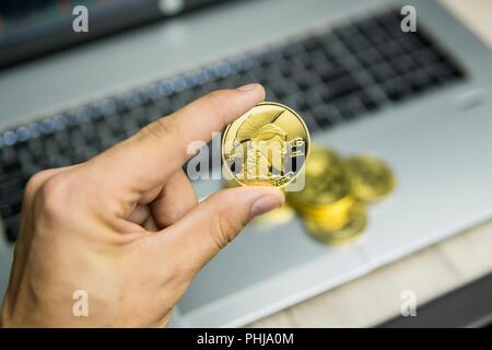 Männliche Geschäftsmann hand Baum titan Bitcoin auf dem Hintergrund der Laptop Tastatur und Stapel von Goldmünzen. Virtuelles Geld und finanzielle Wachstum Konzept. Handel Bergbau von Bitcoins - Stockfoto