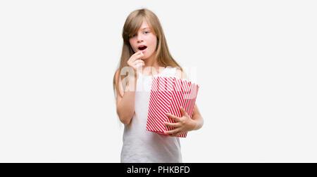 Junge blonde Toddler holding Popcorn pack mit einem selbstbewussten Ausdruck auf Smart Face denken Ernst - Stockfoto