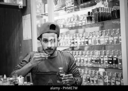 Abu Dhabi, VAE - Juli 24, 2018: ein Shopper dauert ein Schnupfen in einem der vielen Flaschen arabische Parfüms an ein Parfum store in Abu Dhabi, Vereinigte Arabische Emirate - Stockfoto