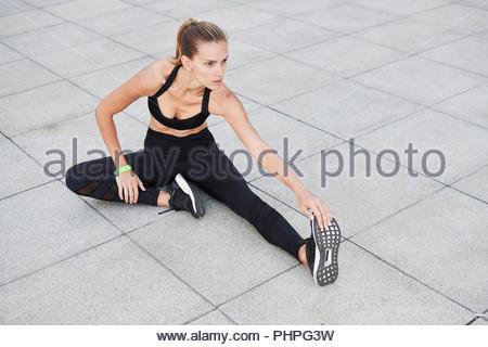 Frau mit schwarzen Sportswear stretching auf Fußweg - Stockfoto