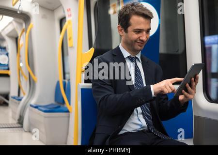 Portrait von Geschäftsmann seine digitale Tablet aufpaßt, während Arbeiten wird - Stockfoto