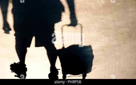 Schatten Silhouette der ältere Mann ziehen einen Einkaufswagen grocery Bag, von der Taille abwärts in sepia schwarz und weiß - Stockfoto