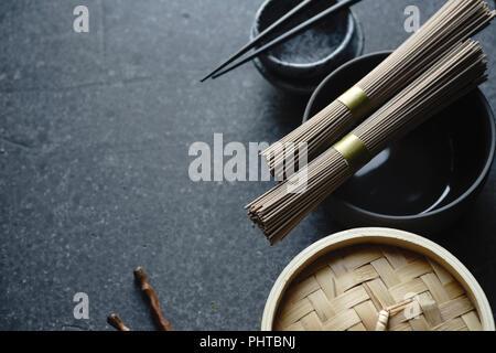Soba Nudeln, Bambus Steamer und asiatische Küche Requisiten auf dunklem Hintergrund mit Kopie Raum - Stockfoto