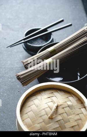 Soba Nudeln, Bambus Steamer und asiatische Küche Requisiten auf dunklem Hintergrund - Stockfoto