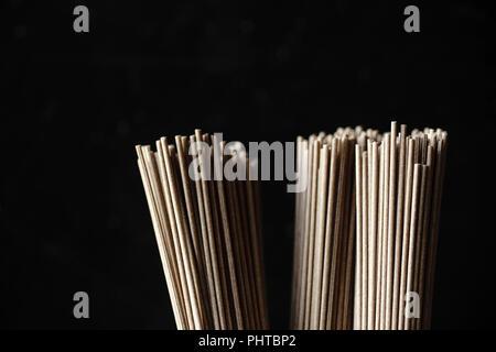 Nahaufnahme von Soba Nudeln, Bambus Steamer und asiatische Küche Requisiten auf dunklem Hintergrund - Stockfoto