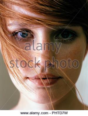 Porträt der jungen Frau mit rotem Haar zerzaust - Stockfoto