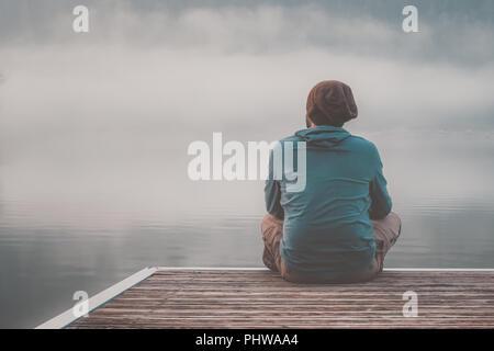 Junger Mann mit Kapuze sitzen auf den Steg eines Sees an einem nebligen Tag. - Stockfoto