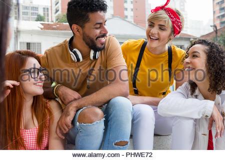 Freunde glücklich lächelnd und Sitzen im Cafe Bar im Freien. Mixed Race Gruppe Geselligkeit in einer Party im Restaurant außerhalb. Sommer, warme, Freundschaft, Taucher - Stockfoto