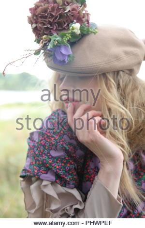 Junge Frau mit Hut mit Blumen - Stockfoto