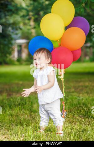 Portrait von cute adorable asiatischen Mädchen Kind ein Jahr alt in weißem Hemd mit Ballons auf dem Feld Wiese Park außerhalb, Konzept der Happy birthday Holiday c - Stockfoto