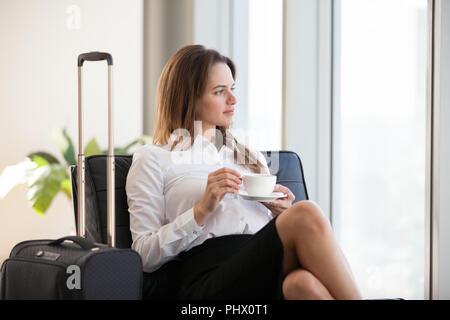 Nachdenklich Geschäftsfrau Kaffee trinken mit Gepäck im Flughafen - Stockfoto