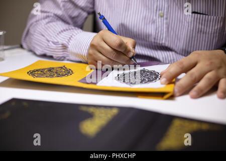Buchen Sie binder Hand illustriert Buch deckt in seiner Werkstatt kalligraphische Muster an seinem Arbeitstisch aus der Nähe zu sehen. - Stockfoto