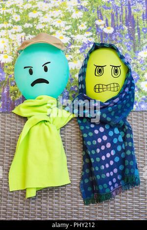 Zwei Ballons mit verärgerten Gesichter und Schals - Stockfoto