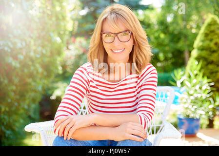 Portrait von zuversichtlich und schöne Frau mittleren Alters Sitzen im Freien und im Garten entspannen. - Stockfoto
